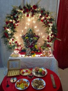 Brown Ganesha with decorated round floweral garland and serial lights